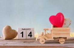 Februari 14th trätappningkalender med träleksaklastbilen med hjärtor som är främsta av den svart tavlan Royaltyfri Foto