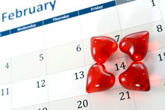 February calendar page and little red hearts marking valentines day Stock Image