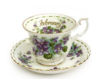 February Cup and Saucer. Month of February Teacup and Saucer Violets royalty free stock photo