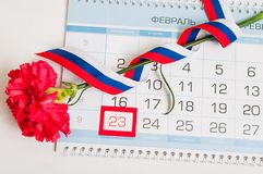 23 February -Defender of the Fatherland Day- card. Red carnation, Russian flag and calendar with framed date 23 February. 23 February card. Red carnation royalty free stock photos