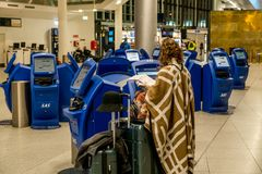 February 18, 2019. Kastrup Airport Denmark Copenhagen. Woman backs unrecognizable with large suitcases baggage independently. Checking in electronic ticket royalty free stock photo