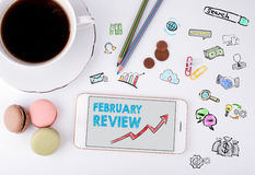 February Review, Business Concept. Mobile phone and coffee cup on a white office desk Stock Photos