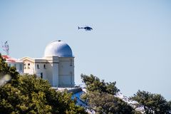 February 27, 2018 San Jose / CA / USA - Fox 2 News helicopter hovers above Lick observatory situated on top of Mt Hamilton on a. Rare winter day with snow stock photos