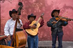 Street musicians in San Migueal de Allende Mexico. February 7, 2016 San Miguel de Allende, Mexico: street musicians performing at a restaurant patio for tips stock image