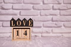 14 february set on wooden calendar with text love on black wooden blocks with white brick background. Happy Valentines day stock photo