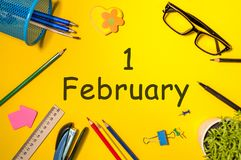 February 1st. Day 1 of february month, calendar on student or some manager workplace, yellow background. Winter time.  Royalty Free Stock Image