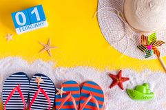 February 1st. Image of february 1 calendar with summer beach accessories and traveler outfit on background. Winter like. Summer vacation concept Stock Photo