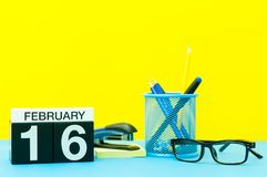 February 16th. Day 16 of february month, calendar on yellow background with office supplies. Winter time.  stock photography