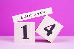 February 14th on pink background. February 14th wooden calendar. February holiday of love stock photo