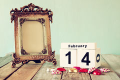 February 14th wooden vintage calendar with colorful heart shape chocolates next to blank vintage frame on wooden table Royalty Free Stock Image