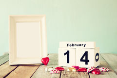 February 14th wooden vintage calendar with colorful heart shape chocolates next to blank vintage frame on wooden table Stock Photography