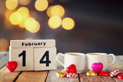 February 14th wooden vintage calendar with colorful heart shape chocolates next to couple cups on wooden table. selective focus Royalty Free Stock Photos