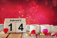 February 14th wooden vintage calendar with colorful heart shape chocolates next to couple cups on wooden table. selective focus Royalty Free Stock Images