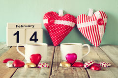 February 14th wooden vintage calendar with colorful heart shape chocolates next to couple cups on wooden table. selective focus Stock Images