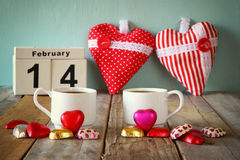 February 14th wooden vintage calendar with colorful heart shape chocolates next to couple cups on wooden table. selective focus Royalty Free Stock Photography