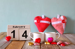 February 14th wooden vintage calendar with colorful heart shape chocolates next to couple cups on wooden table. selective focus Stock Image
