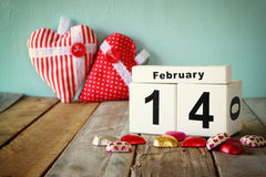 February 14th wooden vintage calendar with colorful heart shape chocolates next to couple cups on wooden table. selective focus Stock Photography