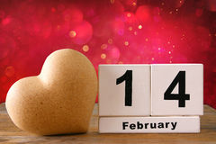 February 14th wooden vintage calendar next to heart on wooden table. glitter background. vintage filtered Stock Image