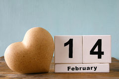 February 14th wooden vintage calendar next to heart on wooden table. vintage filtered Stock Photos