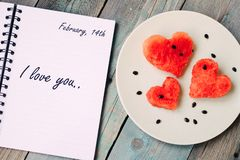 February 14th and words I love you in the notebook, watermelon in the heart shape on vintage wooden table. Top view stock photography