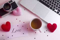 14 February Valentine`s Day red card concept decorated with red and pink heart shaped fabrics on working table with hot tea stock photo