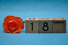 18 February on wooden blocks with an orange rose. On a blue background stock photos