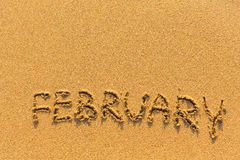 February - word inscription on the gold sand  beach. Stock Photography