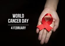 4 February , World Cancer Day with ribbon on human hand for campaign poster about cancer stock photography