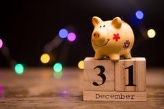 Fecha civil del final de año financiero, el 31 de diciembre con la hucha en fondo oscuro con la guirnalda imagen de archivo libre de regalías