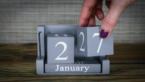 fecha de determinación 27 en el calendario de madera del cubo por los meses de enero almacen de metraje de vídeo