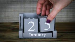 fecha de determinación 25 en el calendario de madera del cubo por los meses de enero almacen de metraje de vídeo