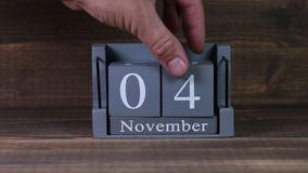 fecha de determinación 04 en el calendario de madera del cubo por los meses de noviembre almacen de metraje de vídeo