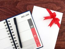 Fecha de diciembre y enero en la página del planificador del diario del calendario y la pluma negra, y sobre blanco de la tarjeta Foto de archivo libre de regalías