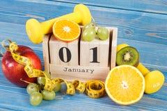 Fecha del 1 de enero en calendario del cubo, las frutas, las pesas de gimnasia y la cinta métrica, Años Nuevos de resoluciones Fotos de archivo libres de regalías