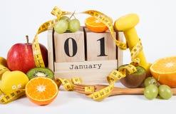 Fecha del 1 de enero en calendario, las frutas, las pesas de gimnasia y la cinta métrica, Años Nuevos de resoluciones Foto de archivo libre de regalías