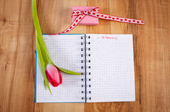 Fecha del 14 de febrero en el cuaderno, el tulipán fresco y el regalo envuelto, día de tarjetas del día de San Valentín Imagenes de archivo
