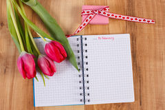 Fecha del 14 de febrero en el cuaderno, los tulipanes frescos y el regalo envuelto, día de tarjetas del día de San Valentín Imágenes de archivo libres de regalías