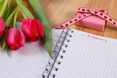 Fecha del 14 de febrero en el cuaderno, los tulipanes frescos y el regalo envuelto, día de tarjetas del día de San Valentín Fotos de archivo