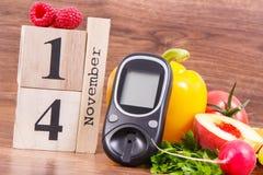 Fecha del 14 de noviembre, del glucometer y de frutas con las verduras, concepto del día de la diabetes del mundo foto de archivo