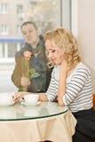 Fecha. La mujer joven espera a un novio en el pequeño café Foto de archivo