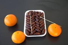 Fecha la naranja en la fruta tropical de la tabla negra Imágenes de archivo libres de regalías