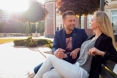 Fecha romántica Adultos jovenes hombre y mujer en un banco en la ciudad Imagen de archivo