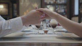 Fecha romántica del hombre y de la mujer en el restaurante Manos de los varones que llevan a cabo las manos de las señoras almacen de metraje de vídeo