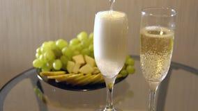 Fecha romántica Derramar el champán en vidrios en una tabla con la fruta almacen de video