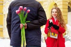Fecha romántica El hombre oculta las flores detrás el suyo detrás para su novia Pares jovenes hermosos que caminan junto a través Foto de archivo