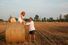 Fecha romántica en recientemente un campo del corte cerca de un pajar Imagen de archivo