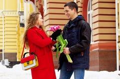 Fecha romántica Hombre que da las flores a su novia Pares jovenes hermosos que caminan junto a través de las calles de la ciudad Fotos de archivo