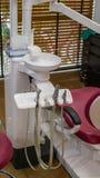 Fechado acima das ferramentas dentais para limpar no suporte da máquina contra a cadeira dental profissional na clínica do dentis imagem de stock