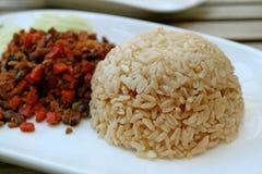 Fechado acima de Brown tailandês cozinhado Jasmine Rice com borrado fez saltar os vegetais servidos na placa branca fotos de stock royalty free