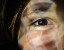 Fechado acima de um olho da mulher com efeito da luz em sua cara fotos de stock royalty free